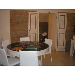 Tavolo in legno massello, piano in legno ad intarsio con colorazione manuale, basamento centrale,  finitura natursbiancata.
